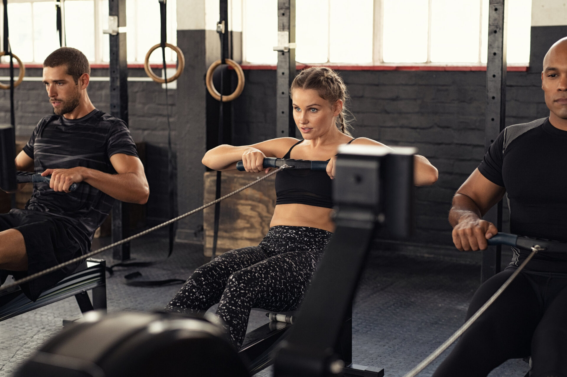 Men and woman in gym using rowing machine